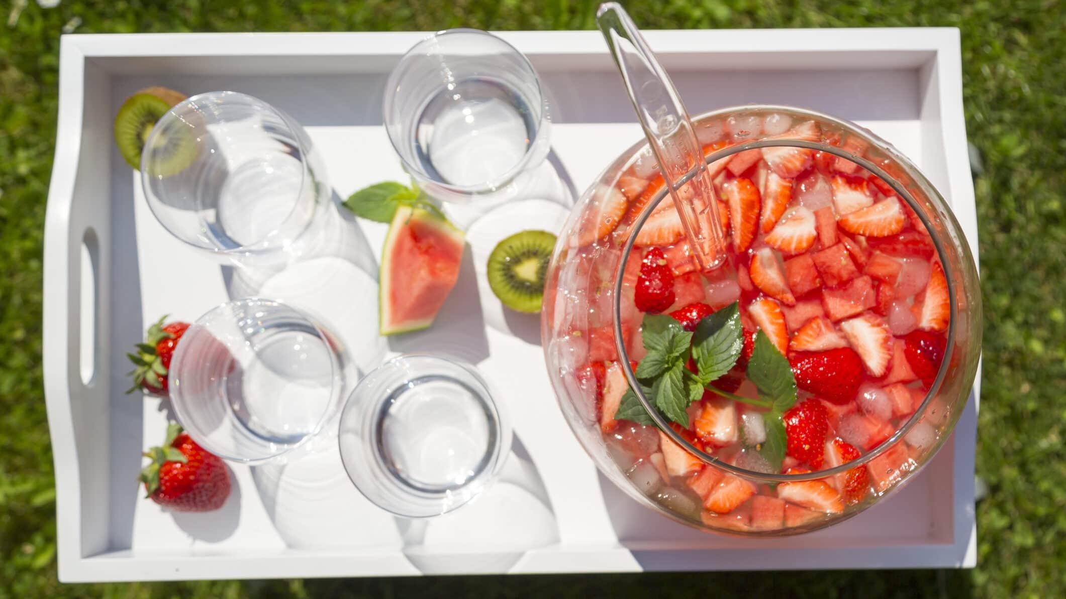 Spritzige Wassermelonen-Bowle in großem Gefäß, daneben Gläser