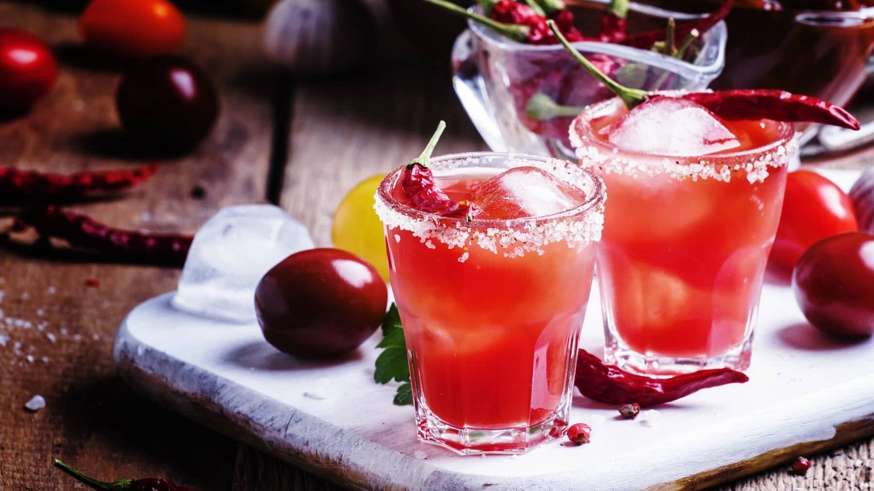 Zwei Gläser mit Chili-Kirsch-Mocktails stehen neben Kirschen und einer Schale voll Chilis