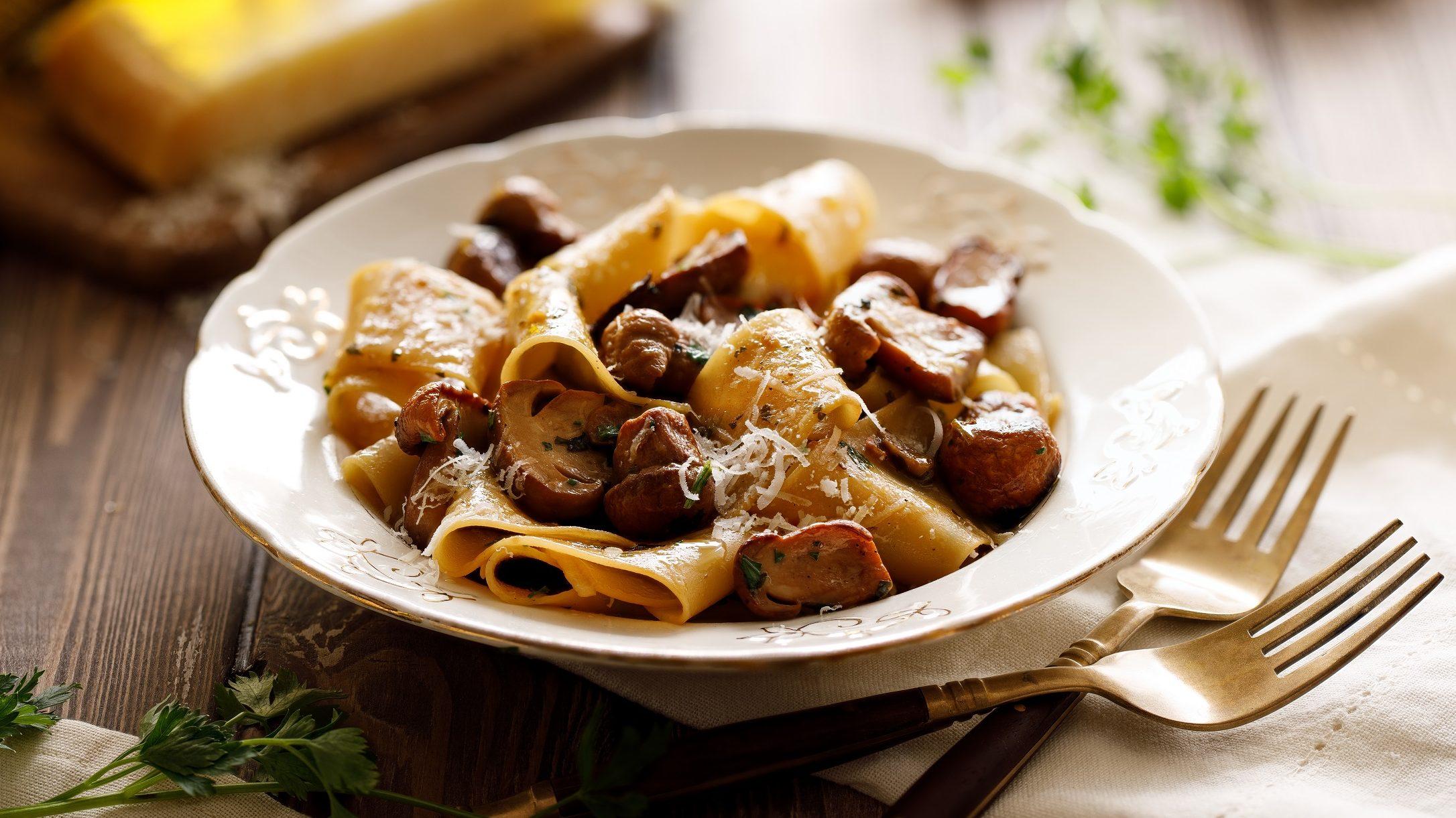 Auf einem rustikalem Holztisch steht ein weißer Teller mit Pappardelle mit Kraeutern und Pilzen.