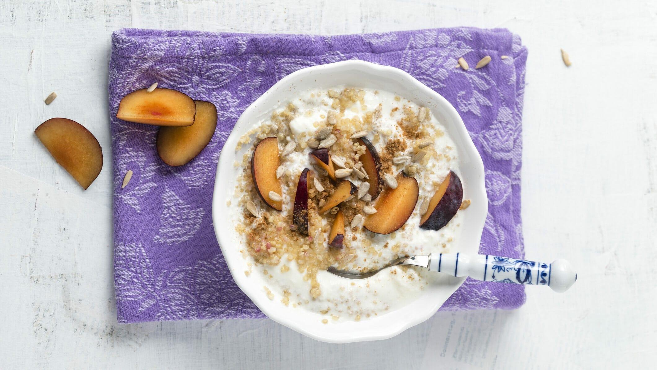 Pflaumen-Frühstücksbrei aus Quinoa mit Joghurt in weißer Schüssel auf lila Tuch