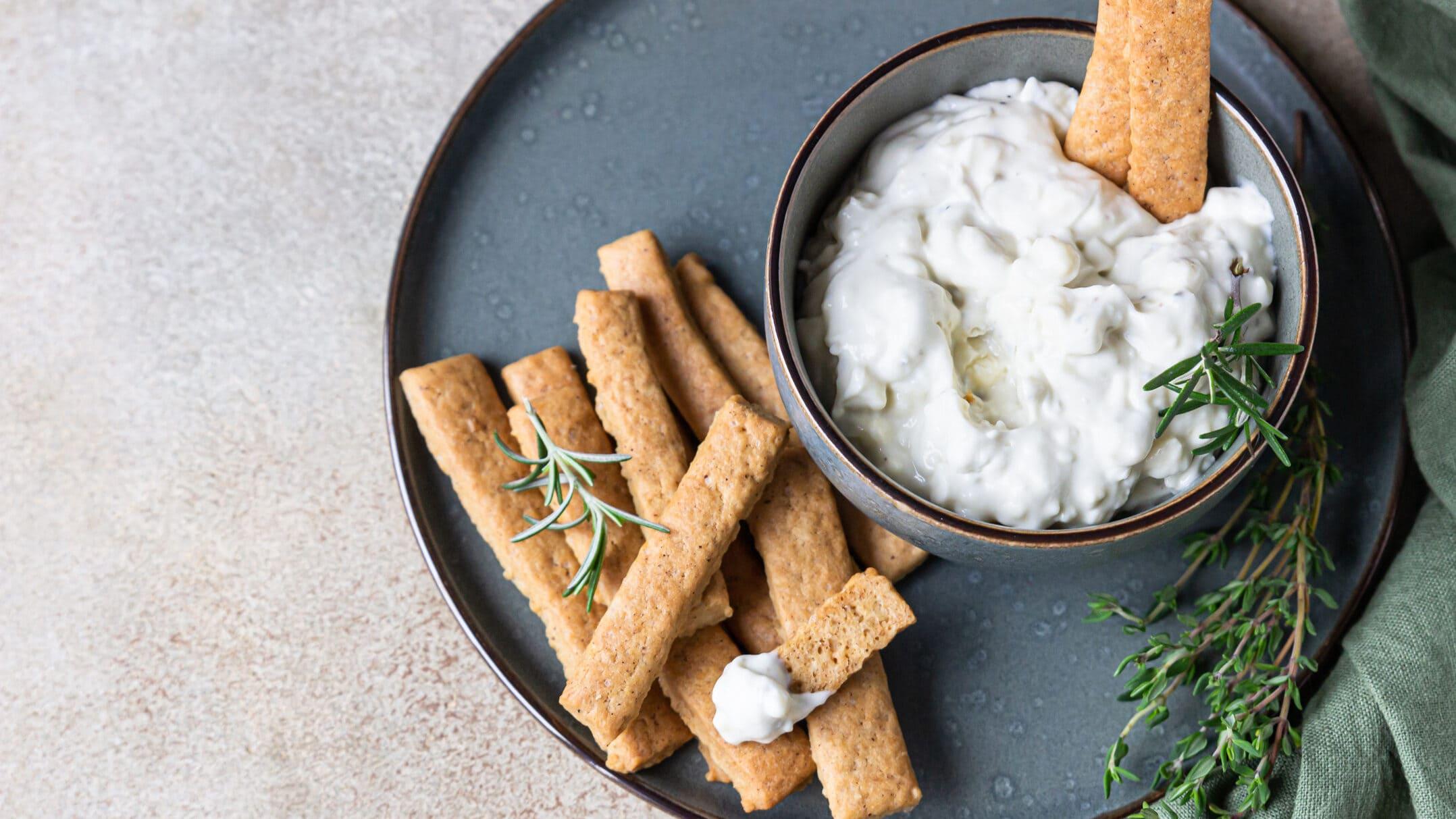 Schneller Birnen-Dip mit Gorgonzola in Schüssel auf blauem Teller, daneben Rosmarin und Brotsticks