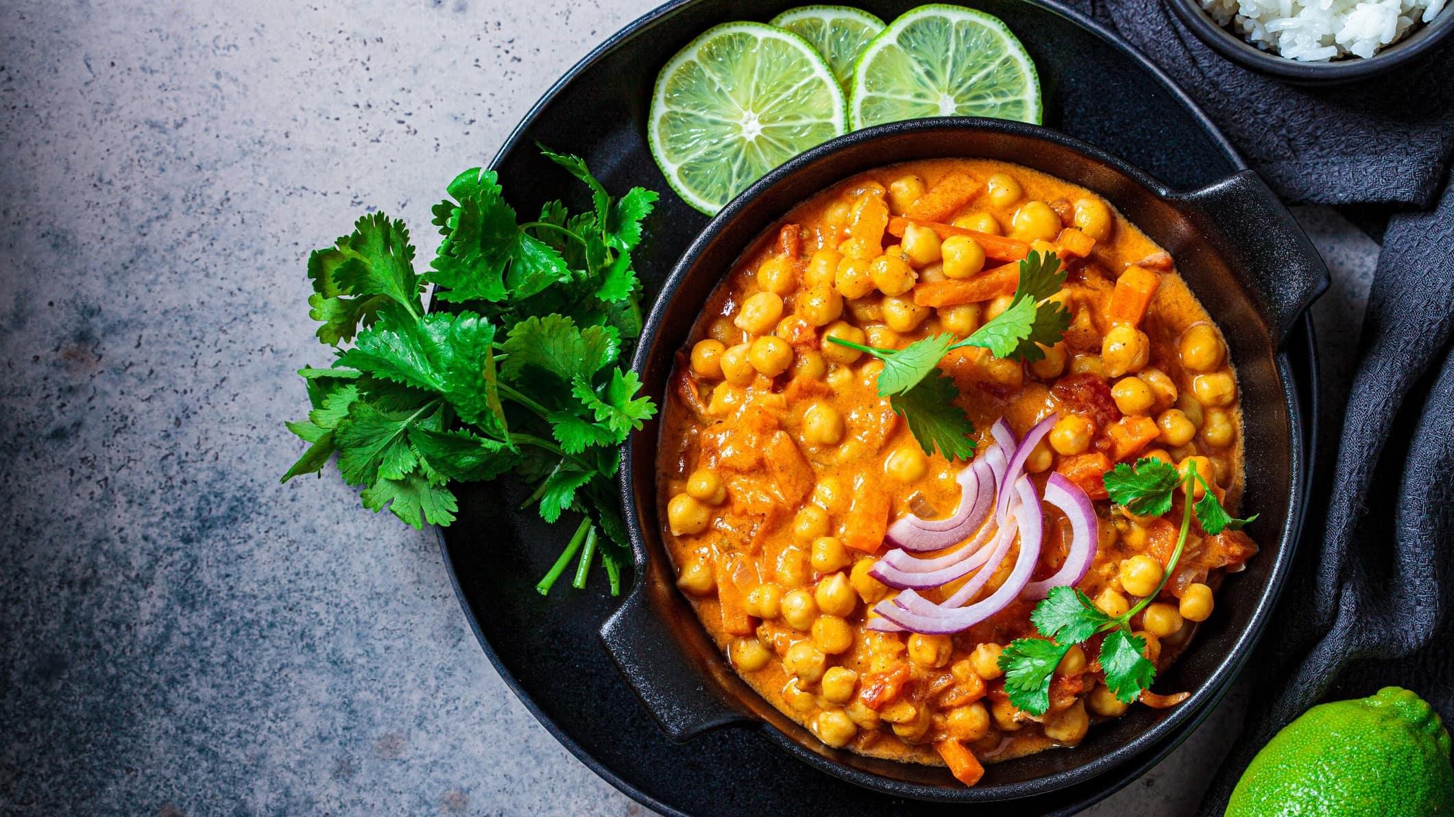 Kichererbsen-Curry mit Limetten auf Teller.