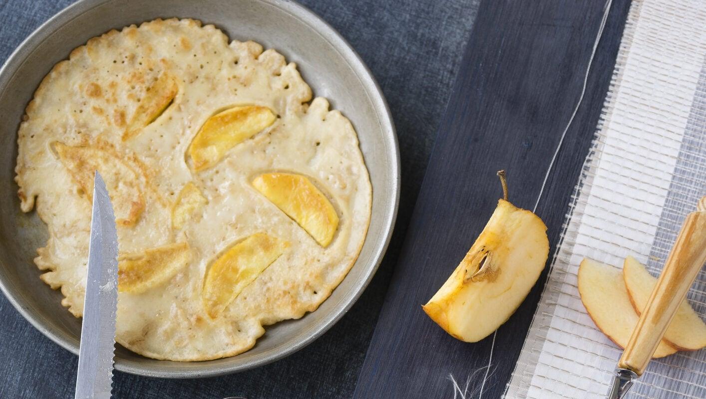 Schnelle Pfannkuchen mit Apfel in Pfanne, daneben Apfel
