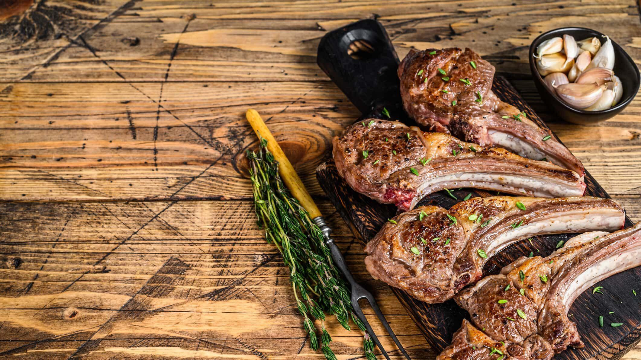 vier gegrillte Lammkoteletts auf Brett, garniert mit einem Stängel Rosmarin und Knoblauchzehen im Hintergrund