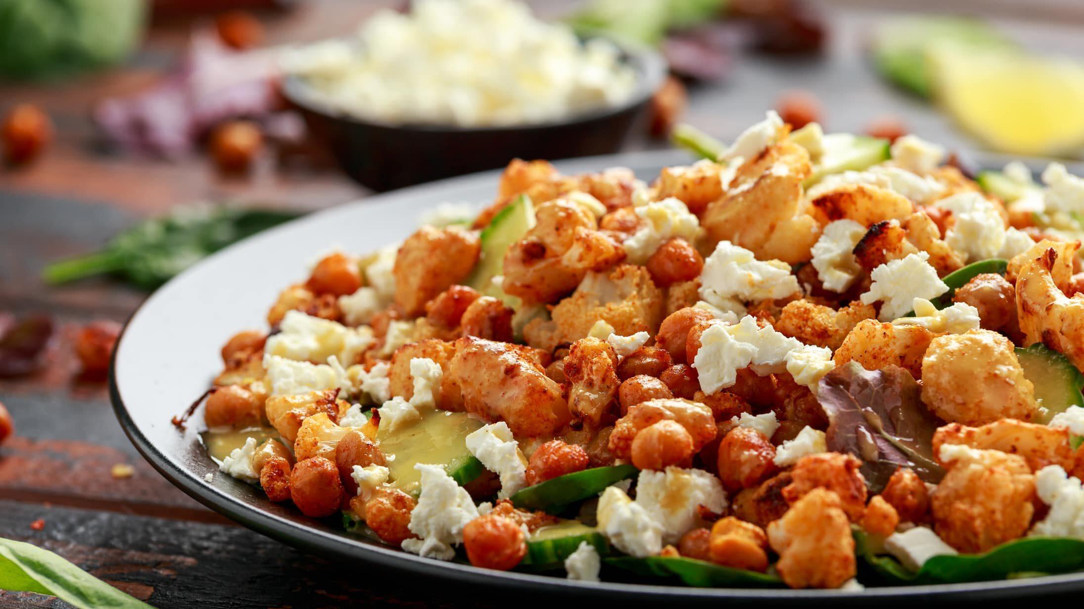 Salat mit geröstetem Blumenkohl, Gurke und Kichererbsen auf dunkler Platte, darüber Feta gebröselt