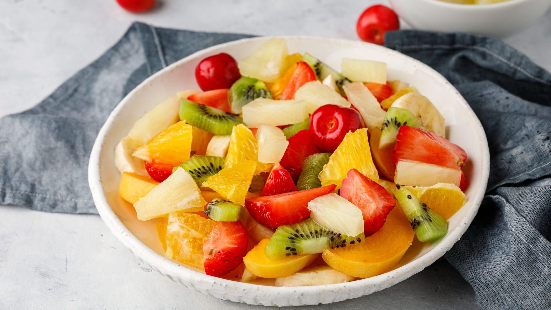 Einfacher Obstsalat mit Vanille in Schüssel, daneben graues Küchenhandtuch
