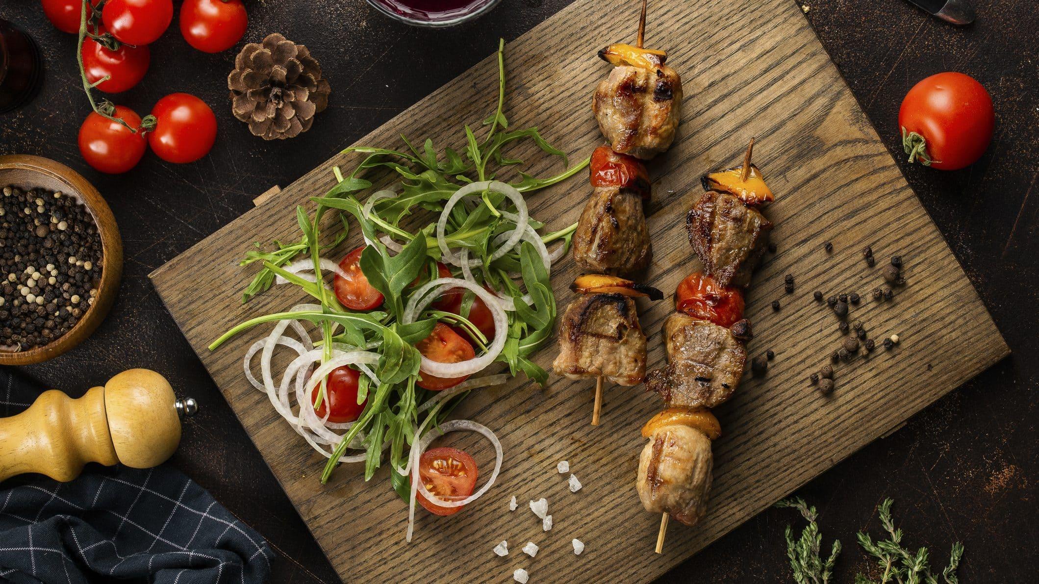 Holzbrett mit würzigen Steak-Spieße mit Rucola-Salat