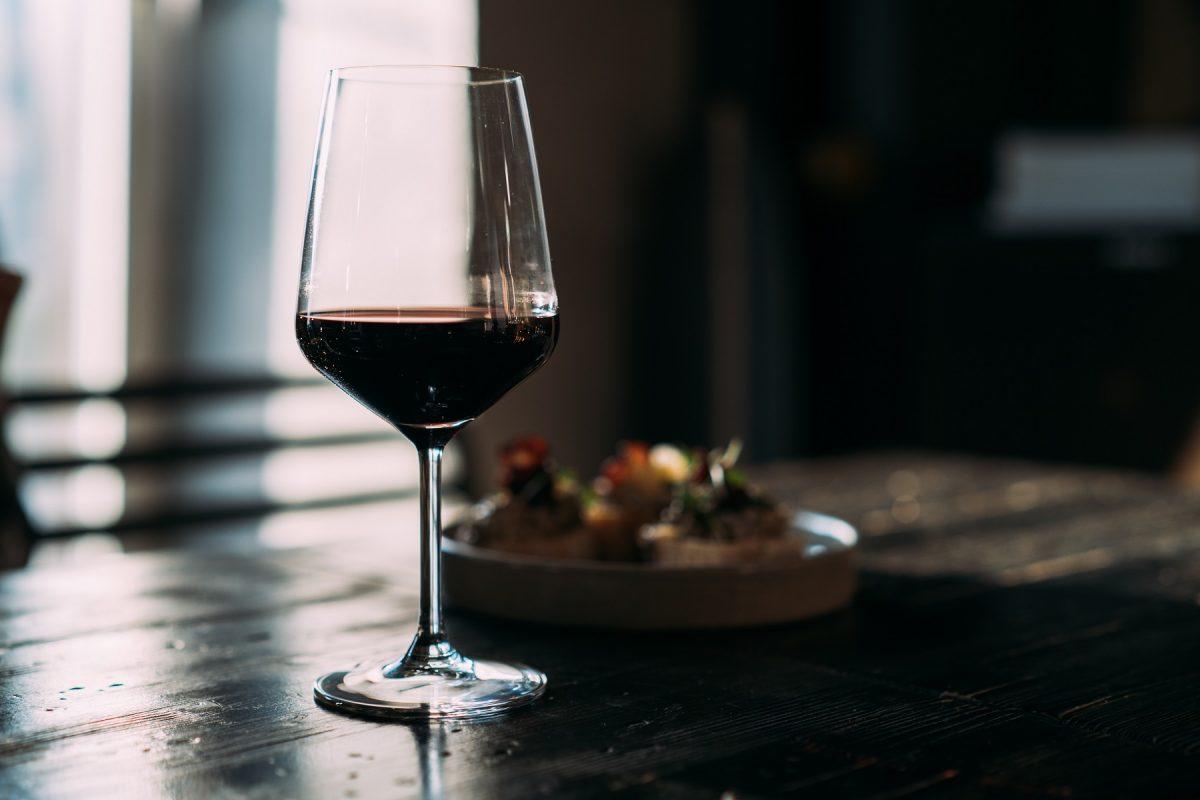 Ein Glas Rotwein auf einem dunklen Holztisch vor einem dunklen Hintergrund.