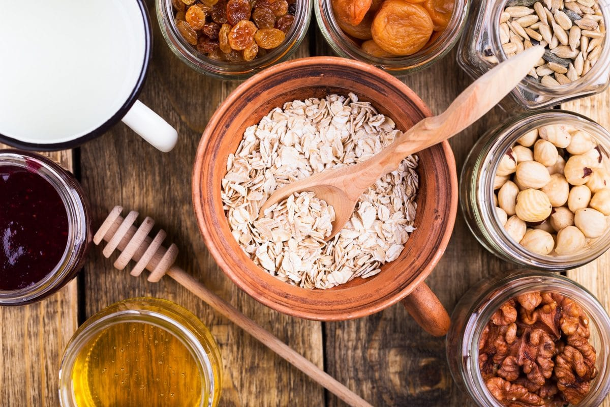Blick von oben auf einen Tisch mit vielen Schüsseln: In den Schüsseln sind Zutaten, um Müsli selbst zu machen, zum Beispiel Haferflocken, Nüsse und Trockenfrüchte
