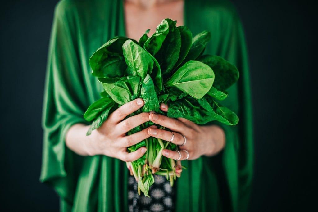 Frau mit frischem Spinat in den Händen