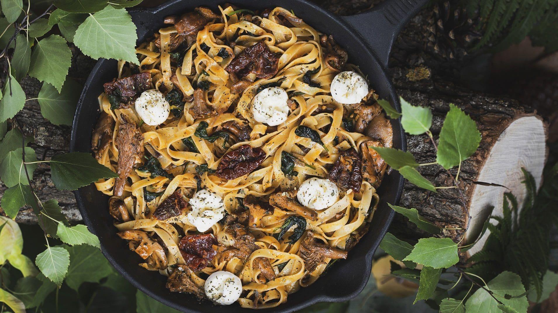 Bandnudeln mit Pfifferlingen und Frischkäsesoße, belegt mit Mozzarella in einer Pfanne.