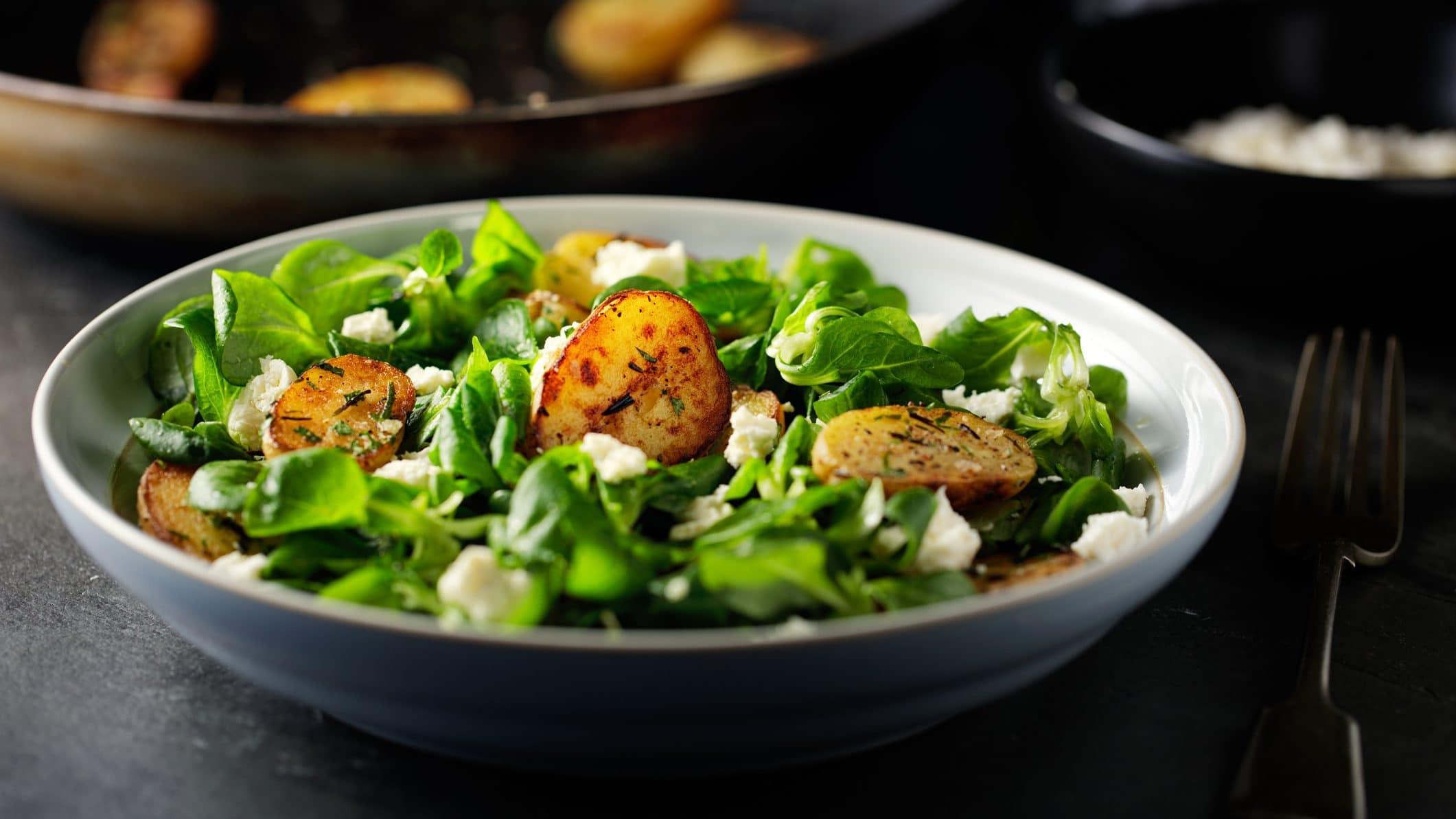 Feldsalat mit Röstkartoffeln und Feta in einer Schale.