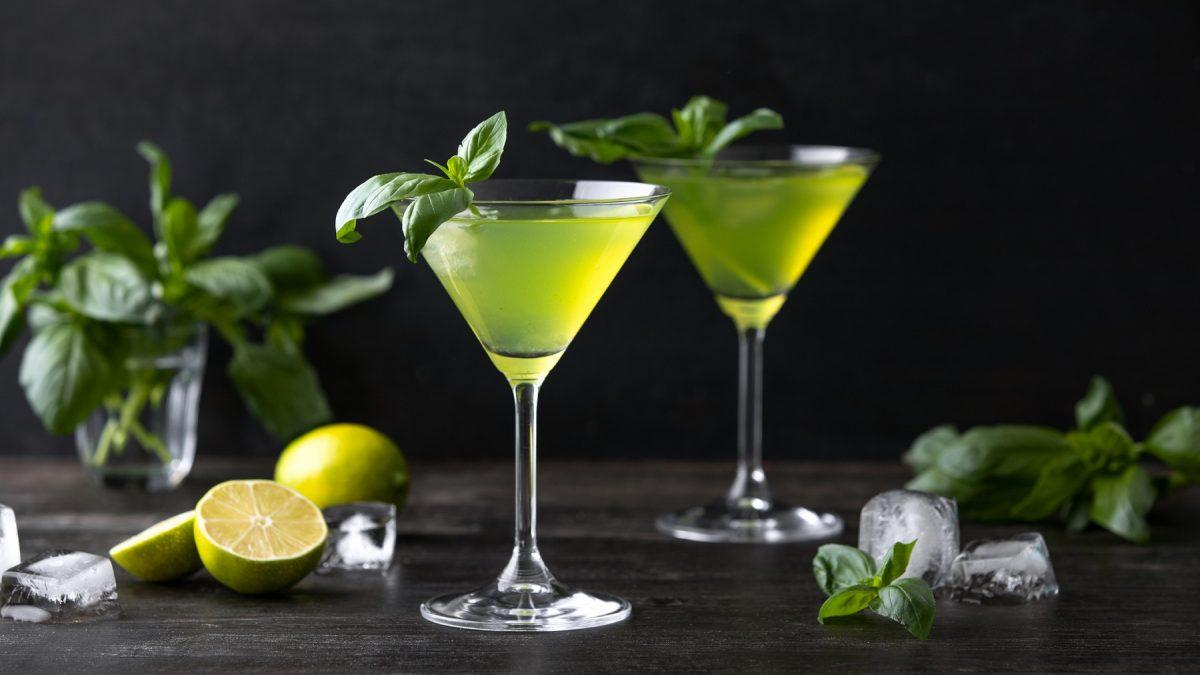 Zwei Gläser mit Gin-Basil-Smash stehen auf einem dunklen Untergrund vor einer schwarzen Wand. Um die Gläser herum liegen Basilikumblätter, angeschnittene Zitronen und einige Eiswürfel. Die Cocktails sind mit Basilikumblättern angerichtet.
