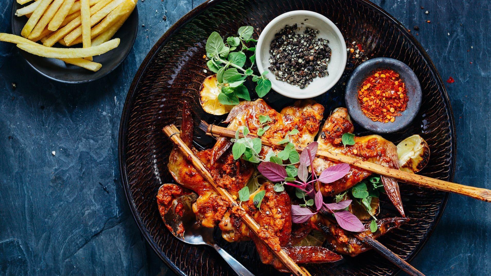 Thailändisches Hähnchen mit Teriyakisoße: ein Teller mit Hähnchenspießen, Gemüse und einer Schale mit Pfeffer- und Chilikörner. Daneben eine Schüssel Pommes.
