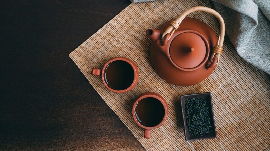 Eine Ton-Teekanne neben zwei Ton-Tassen mit Grünem Tee auf einer Bambus Unterlage von oben.