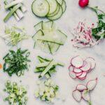 Egalisieren: Verschiedene Gemüsesorten in unterschiedlichen Varianten klein geschnitten, auf Marmorhintergrund, von oben.