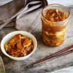 Ein Glas mit fermentiertem Kimchi steht neben einer Schale Reis und Kimchi, daneben liegen Stäbchen.