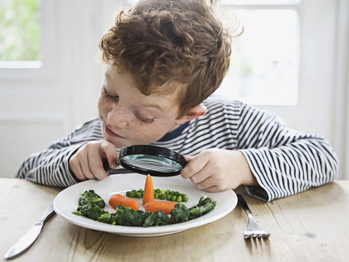 Junge betrachtet sein Essen durch eine Lupe