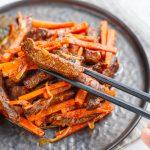 Julienne aus Karotten und Fleisch auf einem grauen Teller, die von einer Person mit grauen Essstäbchen gehoben werden.