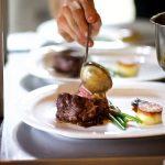 Koch überzieht ein Stück Fleisch mit einer hellbraunen Soße auf einem weißen Teller
