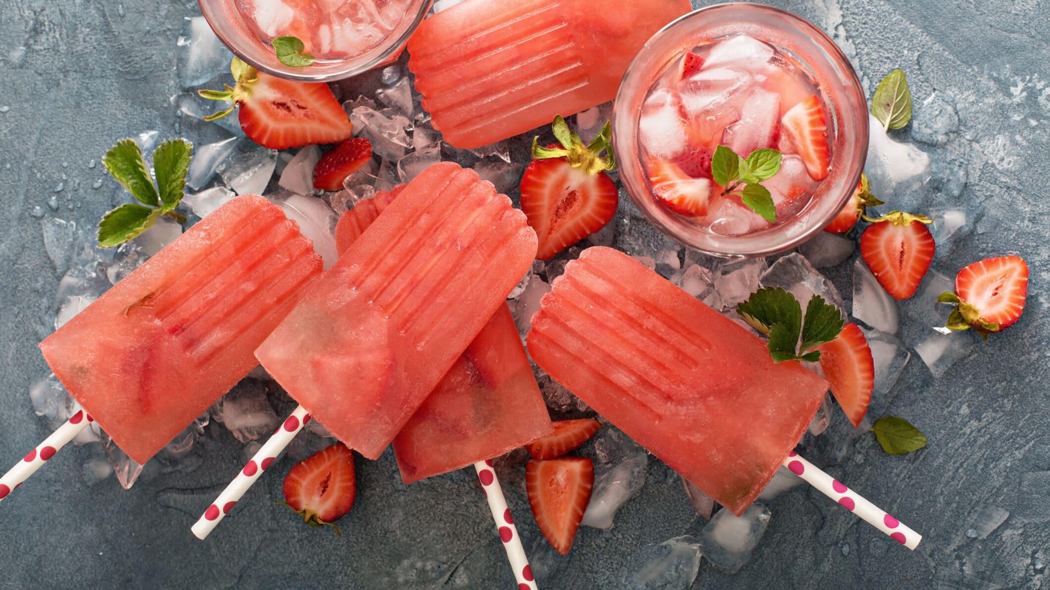 Erdbeer-Margarita Pop-Sicles auf grauer Unterlage, daneben Erdbeeren