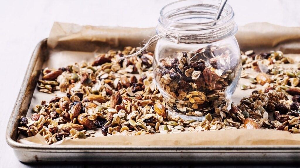 Backblech mit selbstgemachten Müsli, gebackenes Granola aus Haferflocken, Nüssen und Kernen.