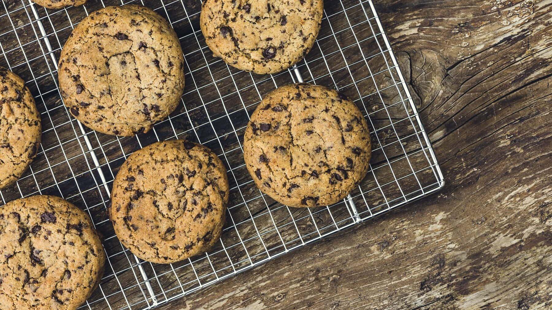 Mehrere runde Chocolate-Chip-Cookies liegen auf einem silbernen Gitter auf einem braunen Holztisch.