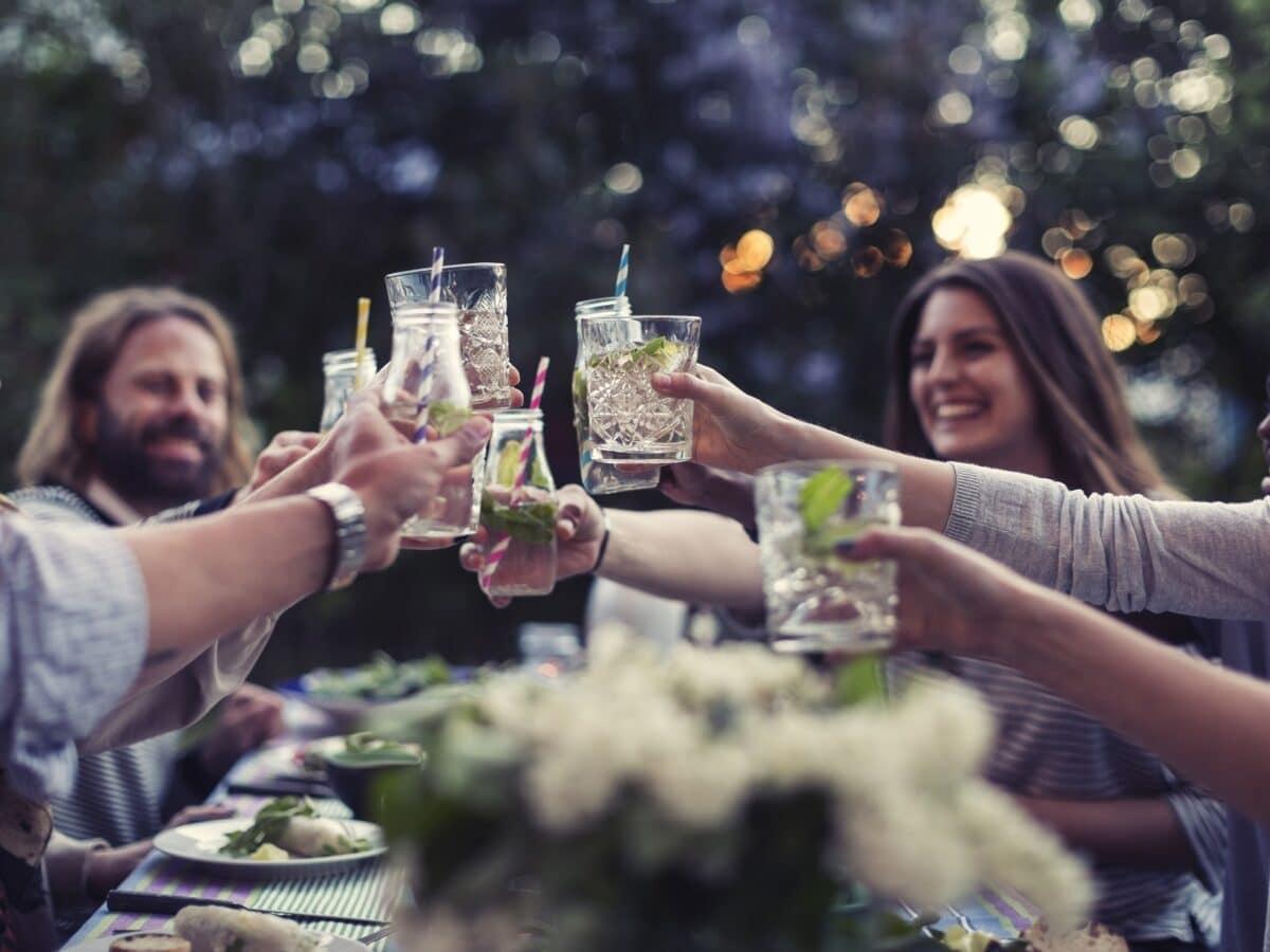 Drinkify: Freunde sitzen um einen Tisch und stoßen gemeinsam an