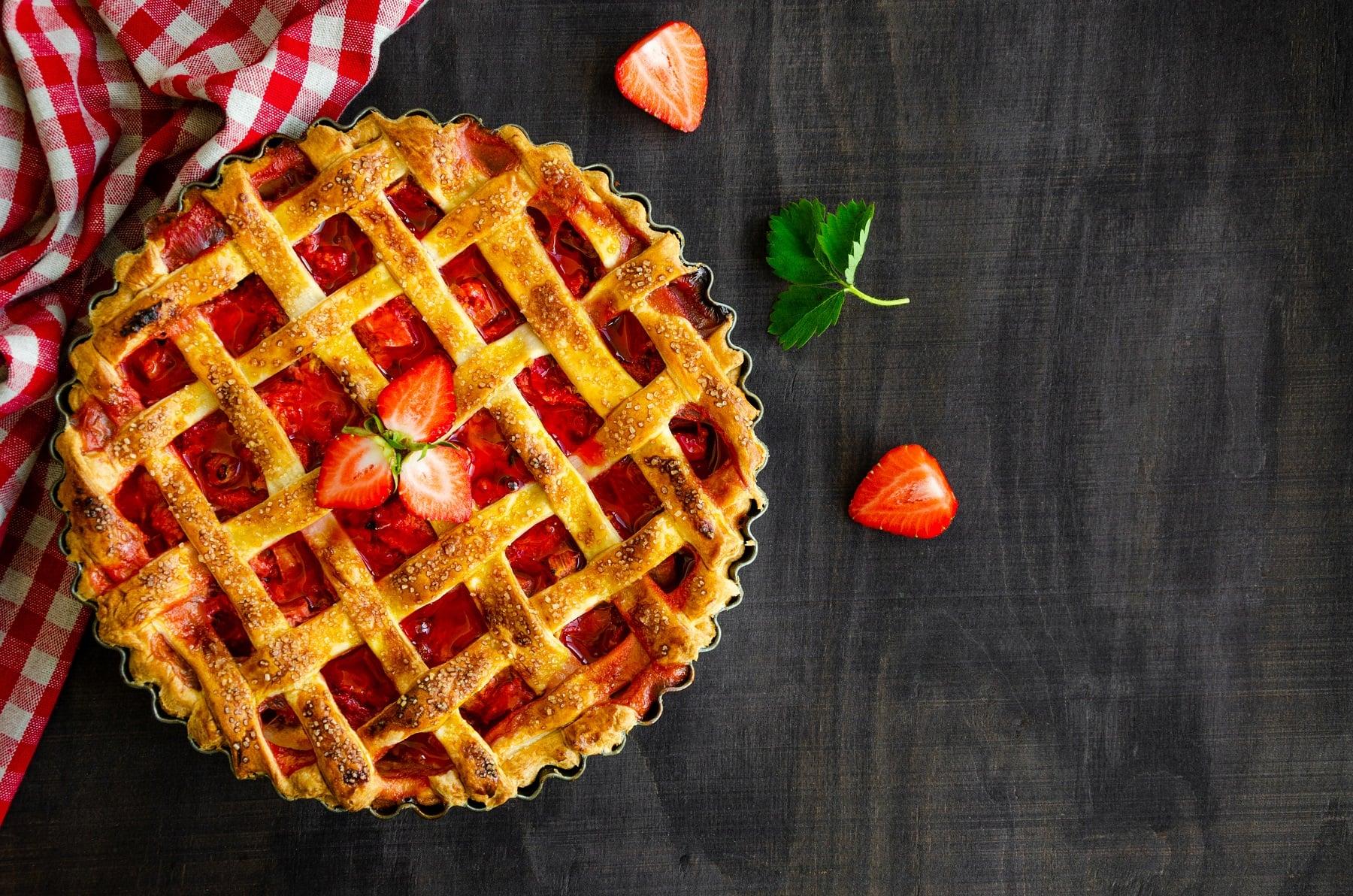 Gitterkuchen mit Erdbeeren und Rhabarber in einer Kuchenform auf einem schwarzen Holztisch neben einer karierten Tischdecke.