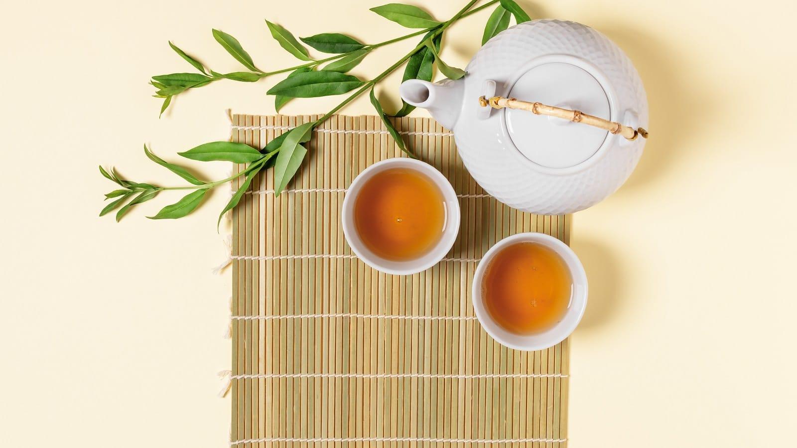 Eine weiße Porzellan Kanne auf einer Bambus-Unterlage neben zwei mit Grün Tee gefüllten Tassen und zwei Zweigen der Teepflanze, von oben vor hellem Hintergrund.