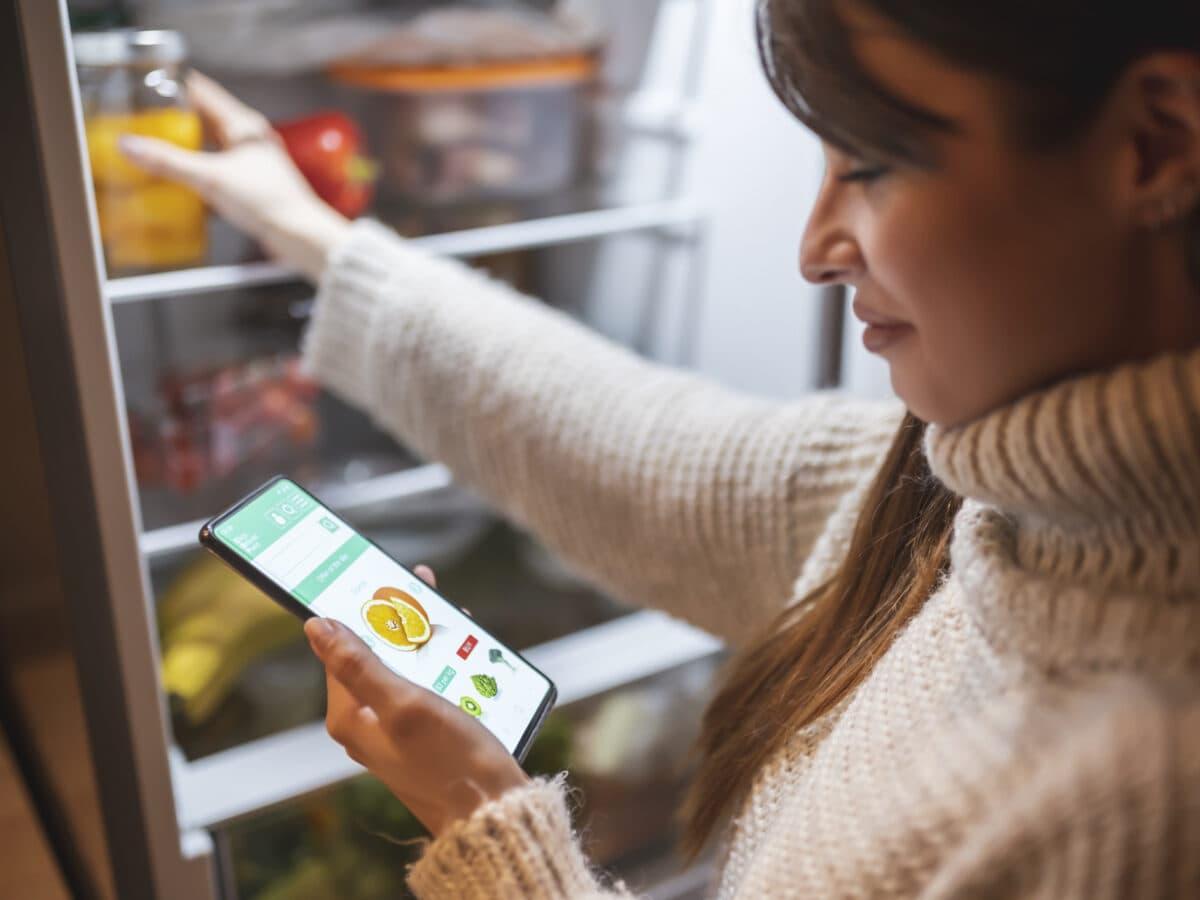 Eine dunkelhaarige Frau steht am geöffneten Kühlschrank und hält ein Smartphone in der Hand, auf dem eine Shopping-App geöffnet ist. NoWaste