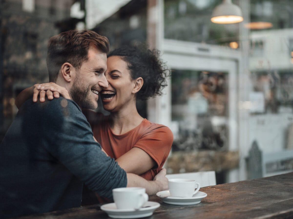 Bumble Brew: Hinter der Glasscheibe eines Cafés umarmt sich ein lachendes Pärchen bei zwei Tassen Kaffee.