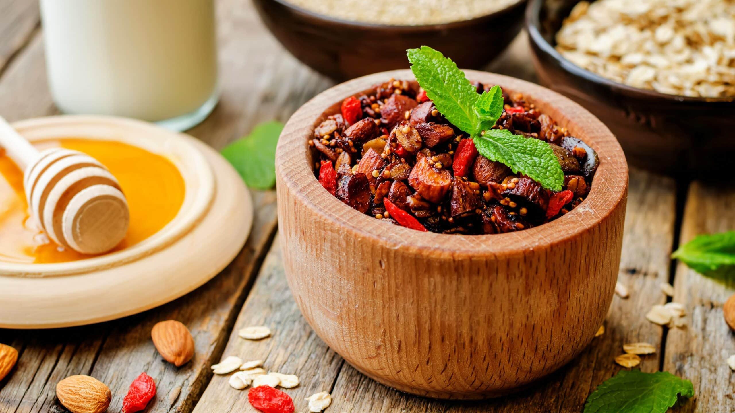 Granola mit Quinoa und Heidelbeeren in einer hellen Holzschüssel neben Honig und Haferflocken auf einem hellen Holztisch.