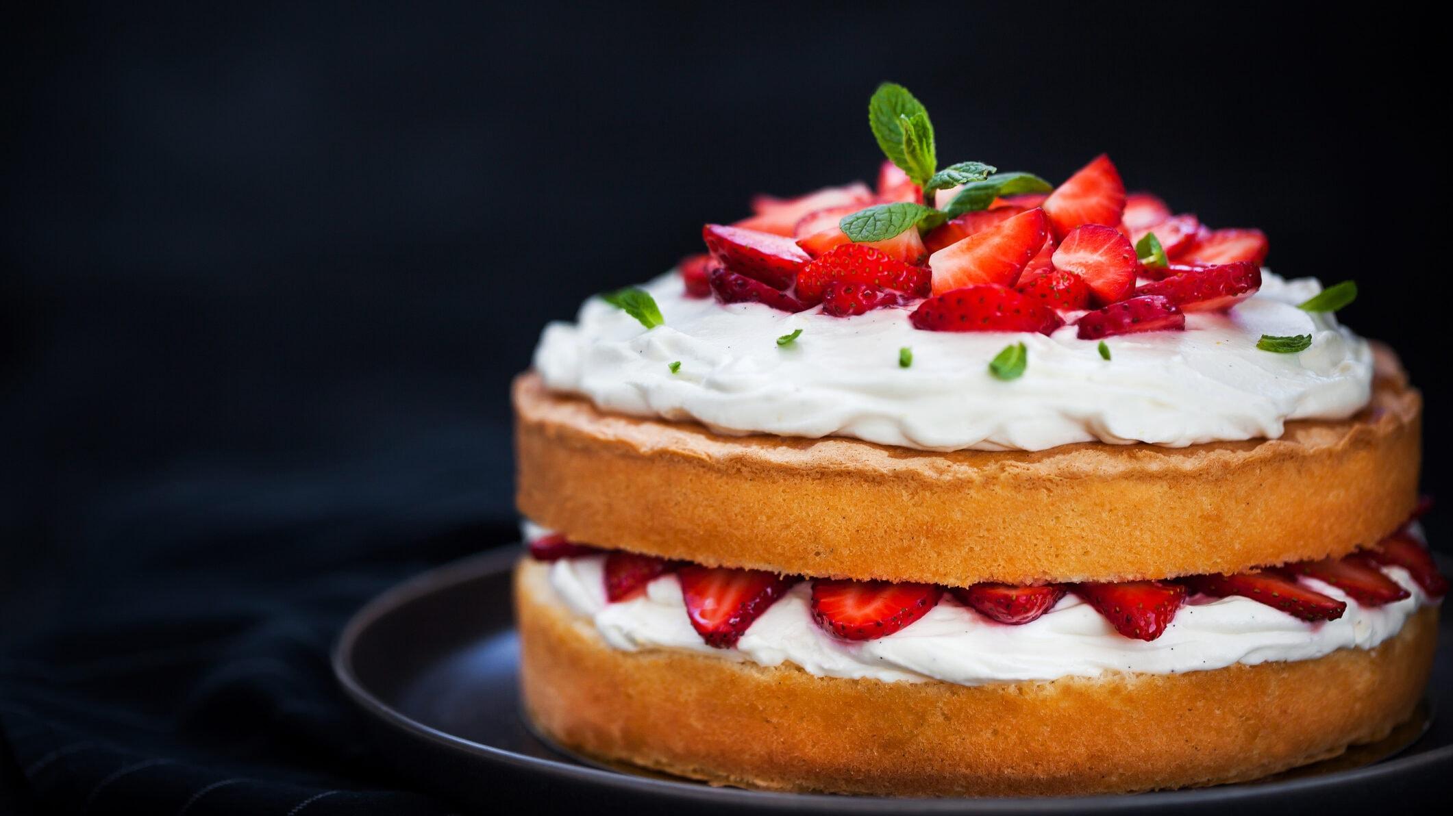 Ein Naked Cake mit Erdbeeren und Sahne auf einem Teller, dekoriert mit frischer Minze.