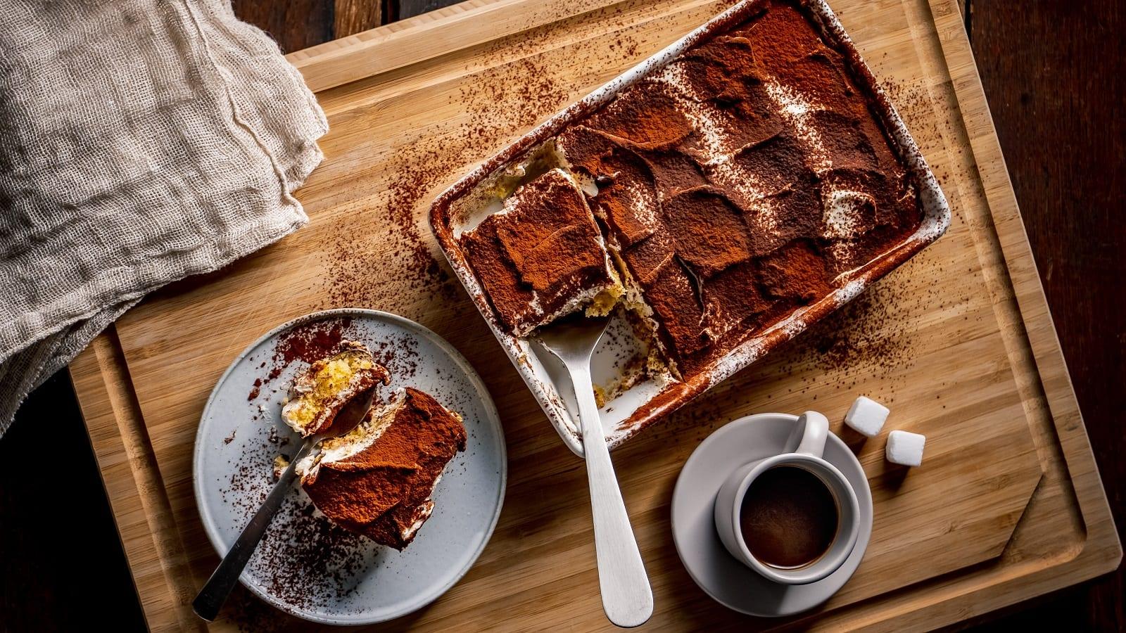 Eine Auflaufform mit klassischem Tiramisu von dem ein Stück herausgeschnitten wurde, das auf dem Teller daneben liegt. Unterhalb der Auflaufform steht eine Tasse Espresso mit zwei Würfeln Zucker. Alles steht auf einem Holzbrett, von oben fotografiert.