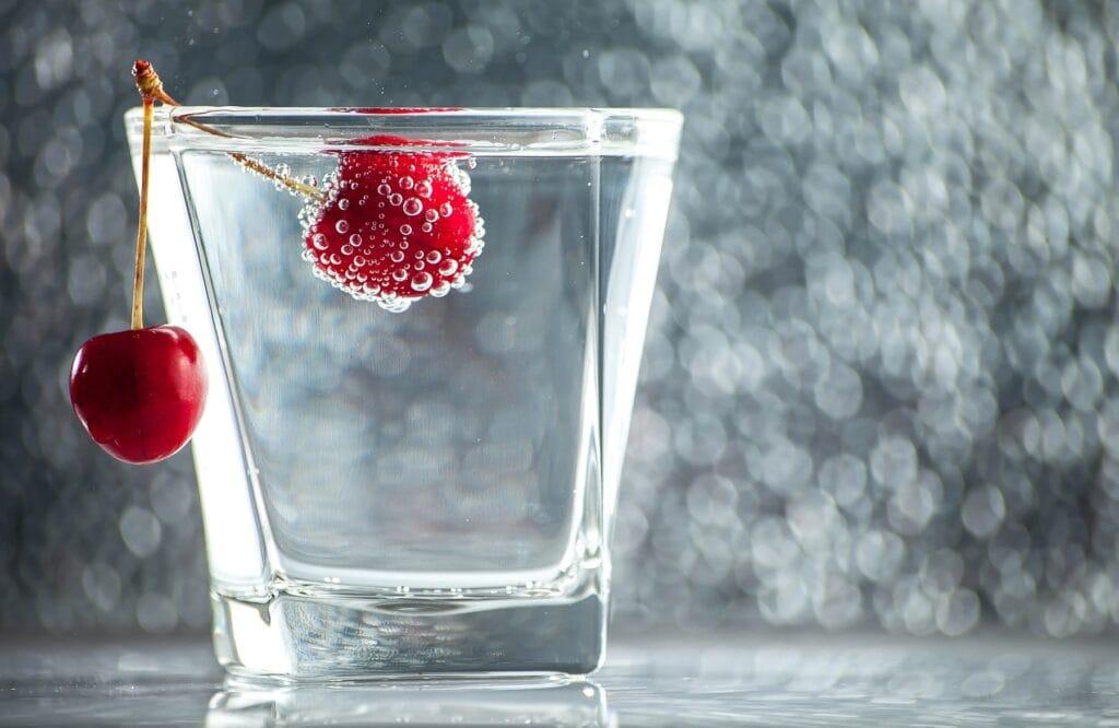 Kirschen liegen am Rand von einem Glas Wasser. Im Hintergrund spiegeln sich Wassertropfen.