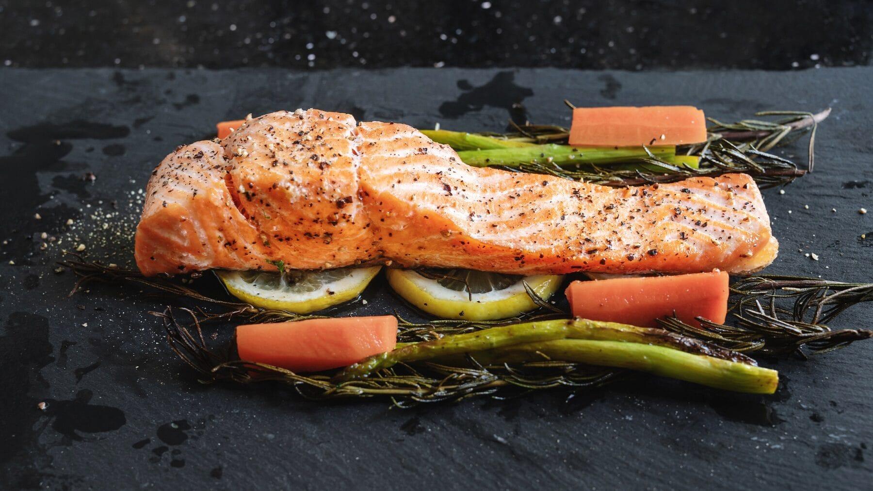 Ein Stück Lachsfilet liegt auf Rosmarin, Zitronenscheiben, Spargel und Karotten. Der Untergrund ist eine schwarze Steinplatte. Über dem Lachs und dem Gemüse sind Salz und Pfefferkörner verteilt.