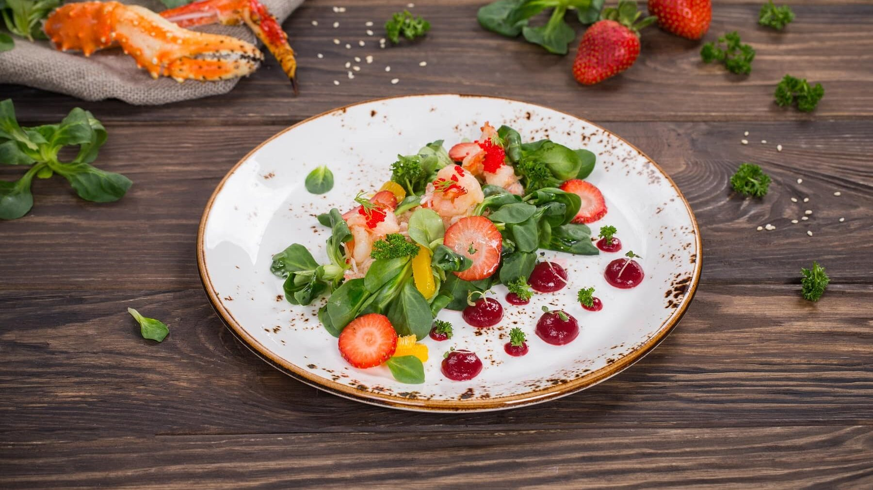 Ein weißer Teler mit Shrimpsalat mit Erdbeeren steht auf einem braunen Tisch. Auf dem Tisch liegen noch Krabben, Salat, Petersilie und Erdbeeren.