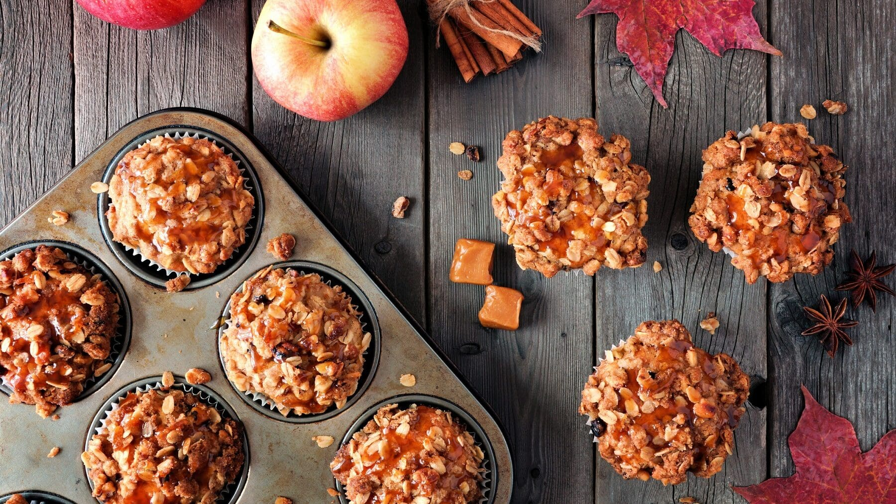 Drei Apfel-Karamell-Streusel-Muffins liegen auf einem grauen Holztisch. Neben ihnen steht eine Muffinform mit weiteren Muffins. Auf dem Tisch verteilt liegen Caramelwürfel, Haferflocken, Äpfel und Zimtstangen.