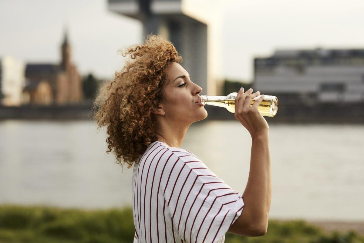 CacaoVida von Ritter Sport: Eine lockige Frau trinkt Limo aus einer Flasche, im Hintergrund ist unscharf ein Hafen zu erkennen.