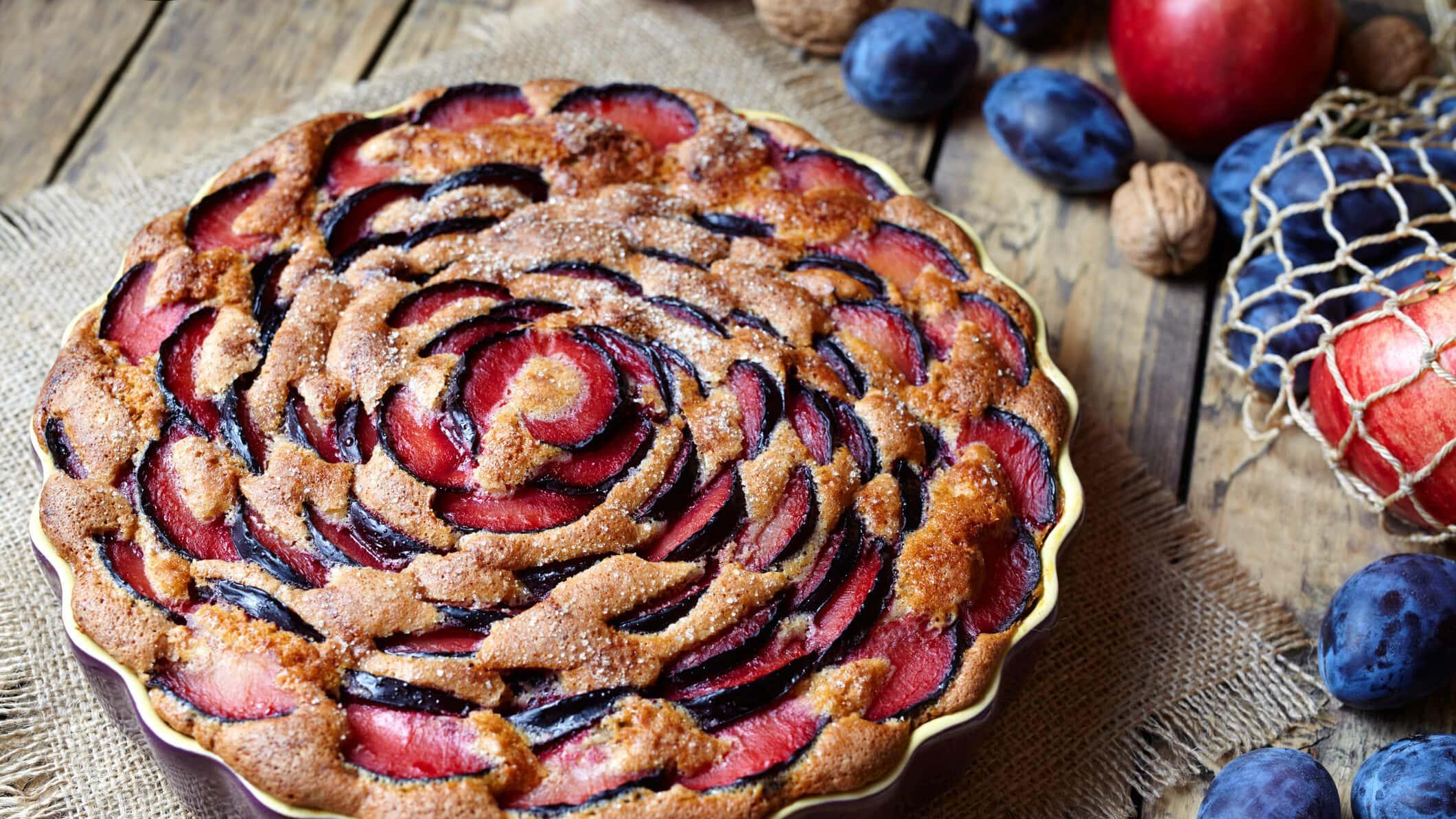 Eine Kuchenform mit Pflaumenkuchen mit Joghurt, daneben liegen Zwetschgen, Äpfel und Nüsse.