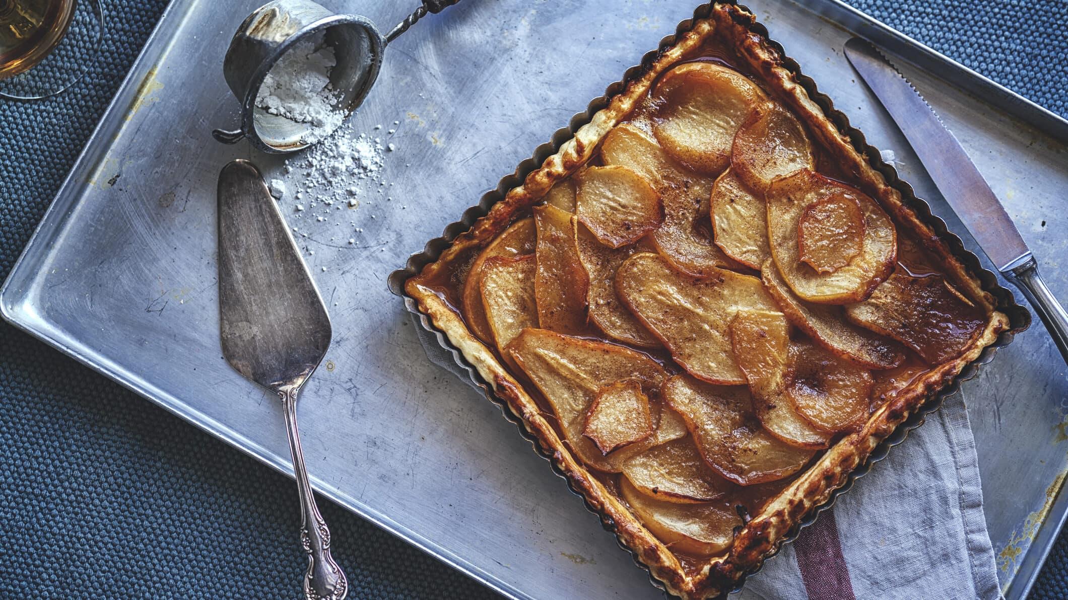 Quark-Birnenkuchen mit Zimt einem Blech, daneben liegen ein Messer, ein Tortenheber und ein Sieb mit Puderzucker.