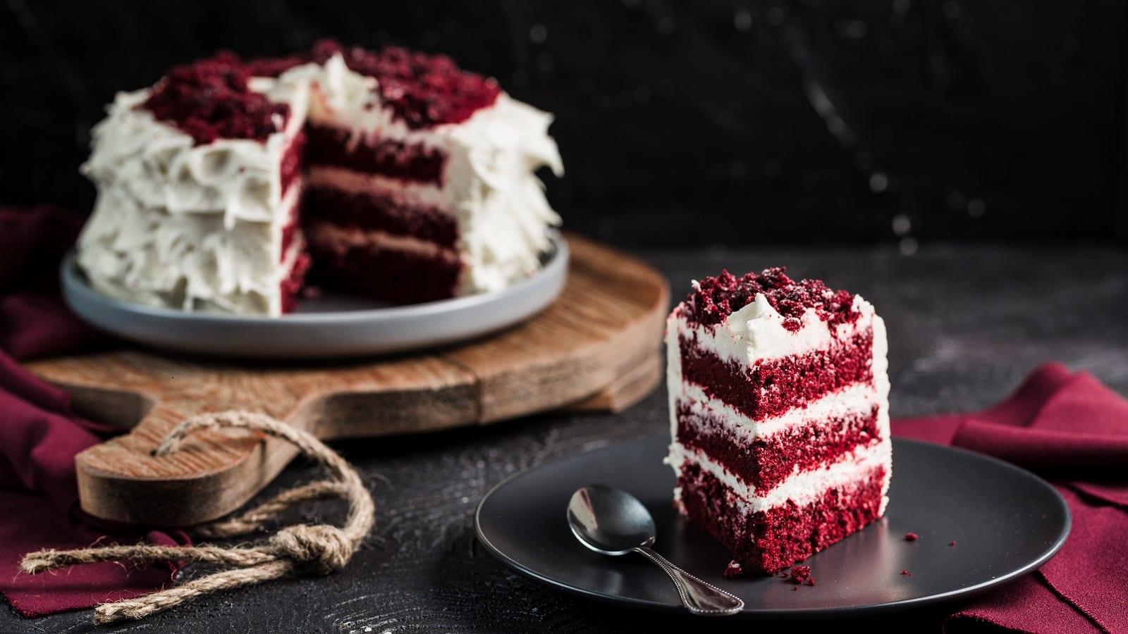 Ein Stück Red Velvet Cake ist auf einem schwarzen Teller angerichtet, zusammen mit einem Löffel. Im Hintergrund sieht man den ganzen Kuchen, dem ein Stück fehlt, auf einem Holzbrett stehen.