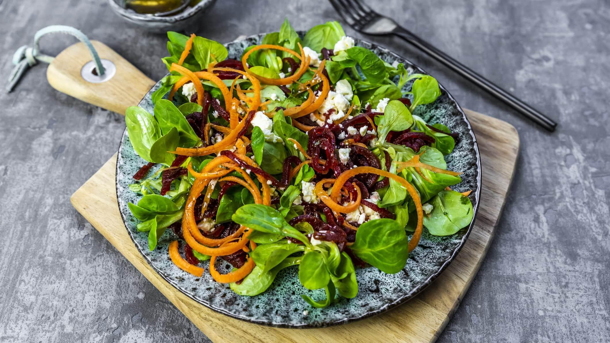 Rote-Bete-Salat mit Feldsalat und Feta auf einem gemusterten Teller. Der Teller steht auf einem Holzbrett. Im Hintergrund liegt eine schwarze Gabel.