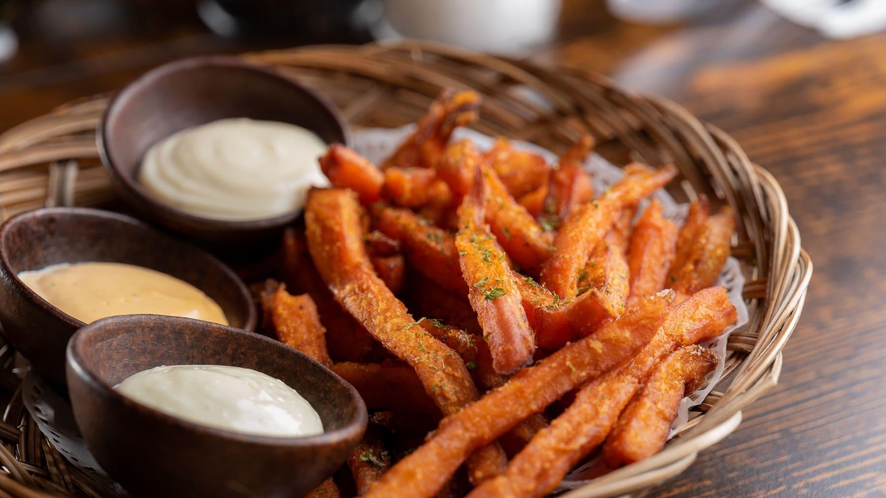 Eine Portion Süßkartoffel-Pommes liegt in einem kleinen Körbchen. Neben den Pommes stehen drei braune Schalen mit verschiedenen Dips. Das Körbchen steht auf einem braunen Holztisch.