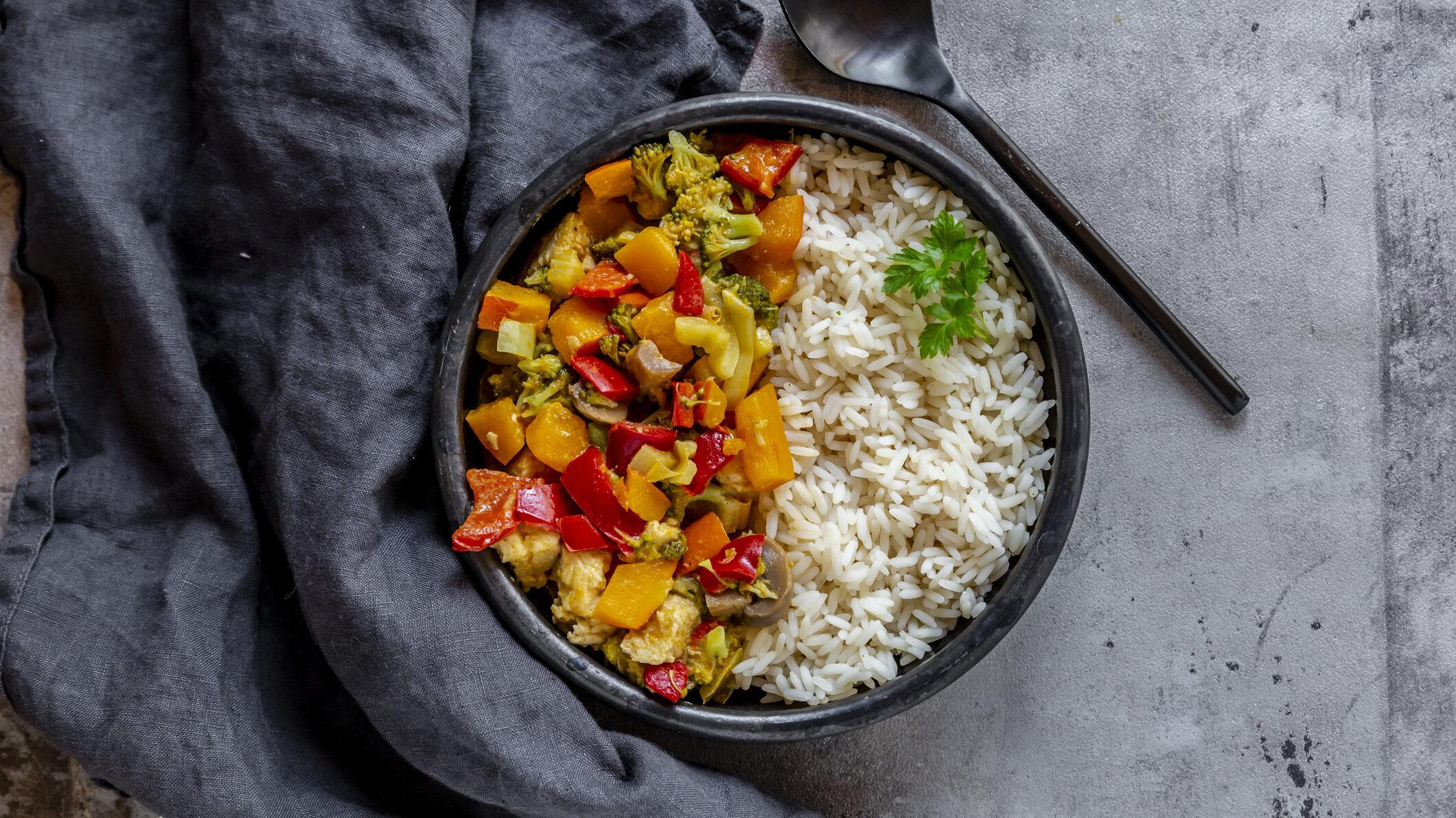Eine dunkle Schale mit vegetarischem Gemüsecurry und Reis in der Draufsicht, daneben liegen ein schwarzer Löffel und ein graues Geschirrtuch.
