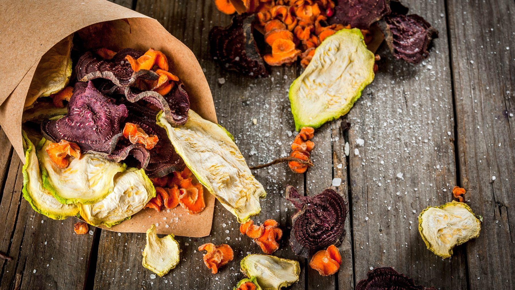 Eine Portion Gemüse-Chips auf einem dunklen Holztisch. Die Chips bestehen aus Zucchini, Möhren und Rote Bete. Auf dem Tisch ist außerdem Salz verteilt.