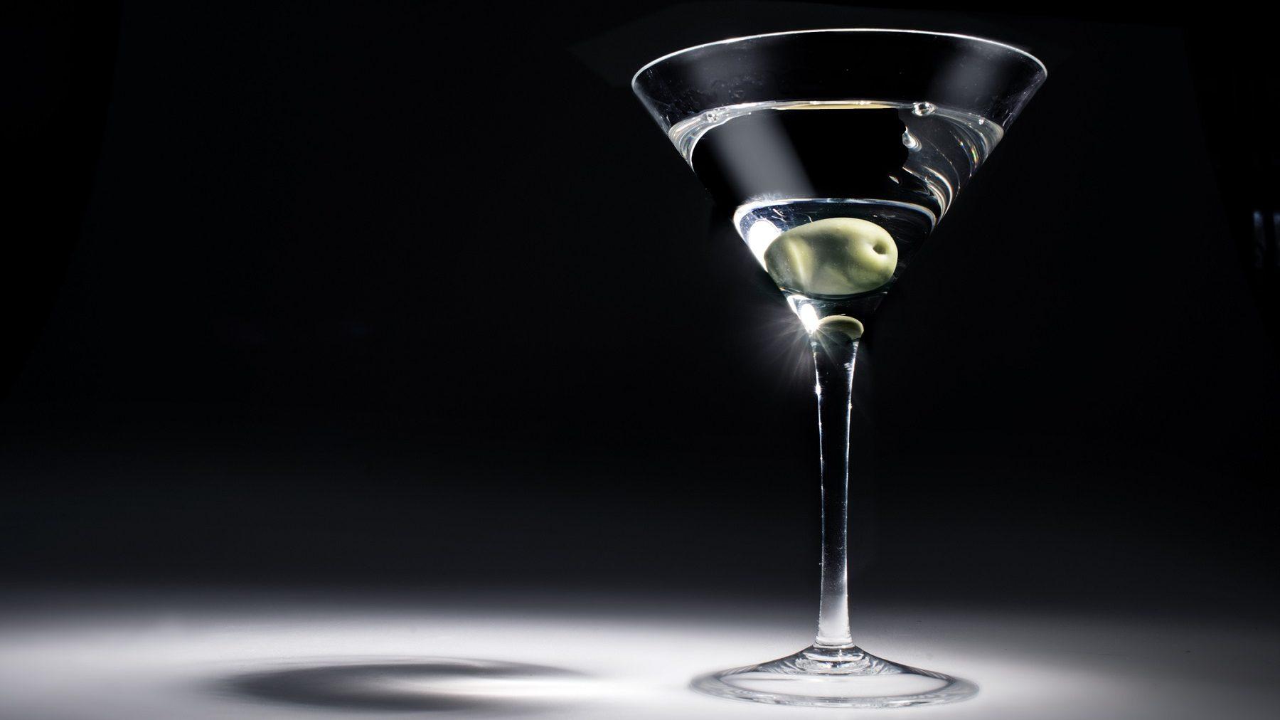 James Bonds Martini mit einer Olive in einem Martiniglas. Das Glas wird aus einer Richtung stark beleuchtet, der Hintergrund und Boden sind dunkel.