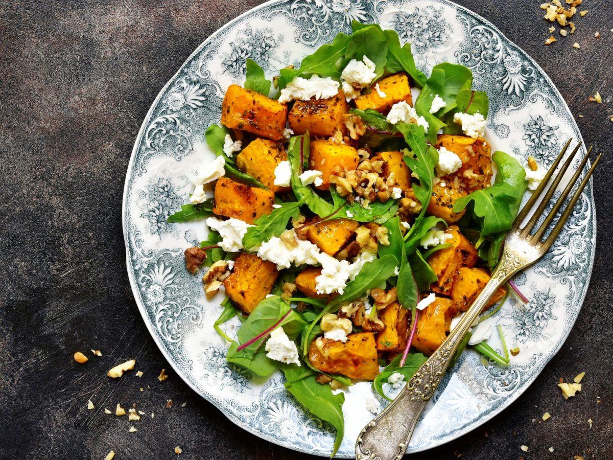 Salat aus Rucola, Kürbis, Feta und Walnuss auf verspieltem Teller