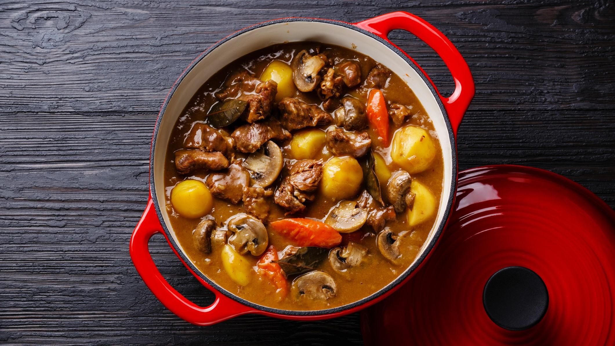 Roter Topf gefüllt mit Pilzgulasch mit Kartoffeln und Gemüse auf dunklem Holzuntergrund.